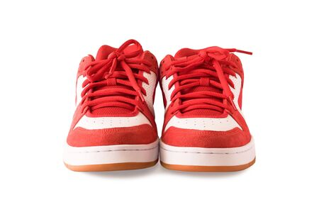 Front view of pair of red gumshoes or skate shoes isolated on white Imagens