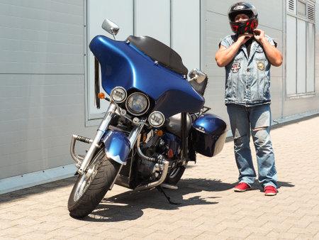 Sochi, Russia - June 14, 2019: Adult biker standing next to motorcycle and wearing helmet