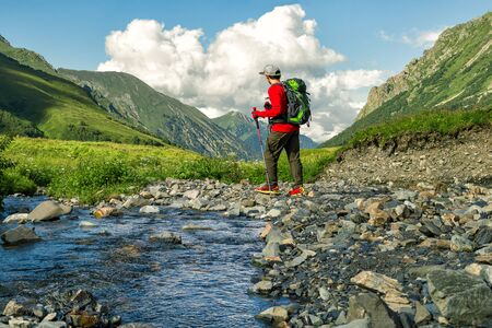 Young active hiker with backpack and trekking sticks walking along river at mountains background
