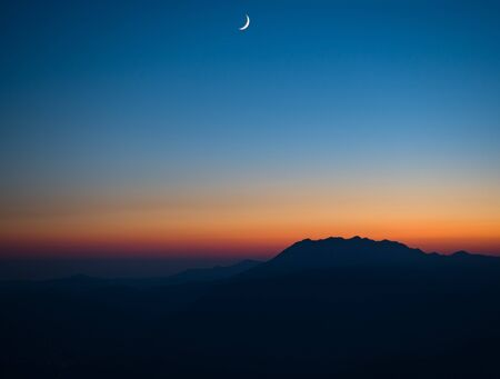 Panoramic view of sunset and night sky with new moon at mountains silhouette background