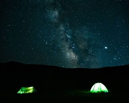 Panoramic view of night sky with Milky way and light camping tents at mountains silhouette background