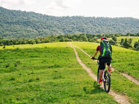 Back view of active bicyclist with backpack riding mountain bike on path at green meadows background at sunny summer day