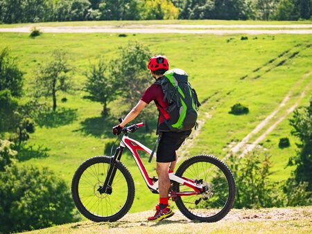 Active man with backpack riding full suspension bicycle on trail at natural background Фото со стока