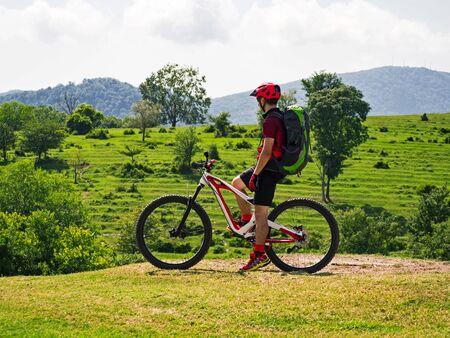 Side view of sports man on mountain bike at rural alpine fields background Фото со стока
