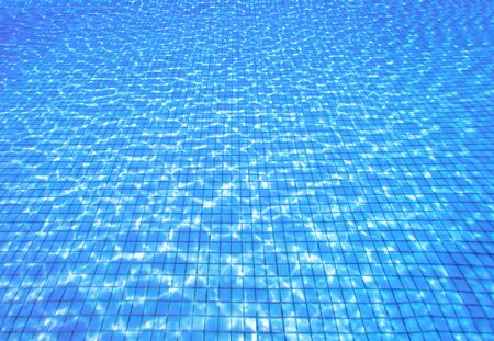 Top view of blue water ripples in swimming pool. Summer background with copy space
