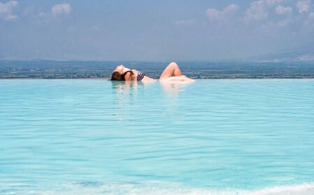 Young caucasian woman in bikini relaxing in blue thermal water outdoors. Spa and beauty treatment background