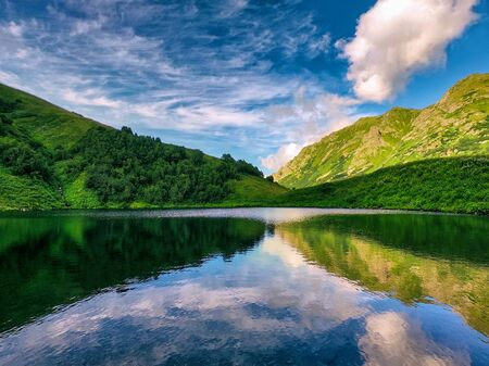 Panoramic view of calm surface of mountain lake at blue sky background with clouds Stock fotó