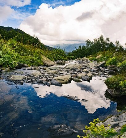 Clouds reflection on river or creek water surface. Natural background with mountains Banco de Imagens