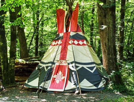 Wigwam at forest background. Conical dwelling of Native Americans 免版税图像