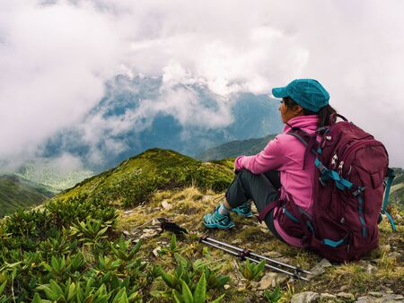 Young active woman with backpack sitting, relaxing and looking at mountains background