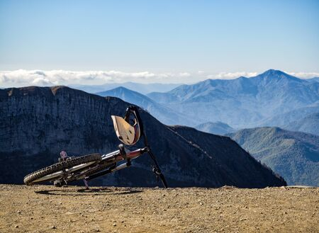 Bicycle with full-face helmet at mountains background. Full suspension bike for extreme downhill riding