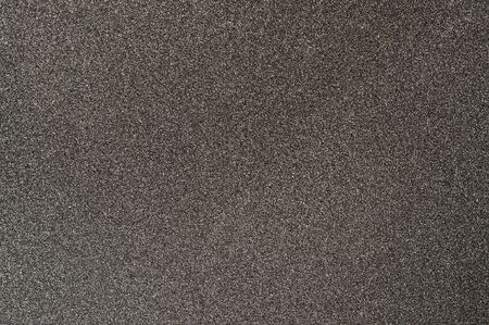 Black sandpaper textured background. Coated abrasive for making surface rougher