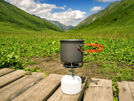 Food or drink preparation in cooking pot on camping gas stove at mountains valley background at summer sunny day
