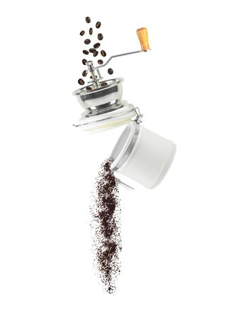 Coffee beans and ground powder falling from manual grinder. Ingredient for hot drink isolated on white background