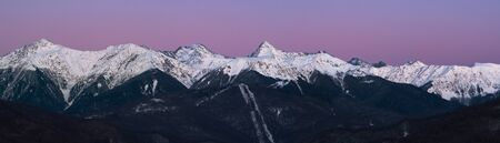 Panorama of snowy mountains ridge at pink and blue sky background at sunset. Krasnaya polyana, Caucasus, Russia
