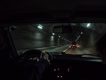 View inside of car moving in road tunnel. Hand of man on steering wheel driving automobile