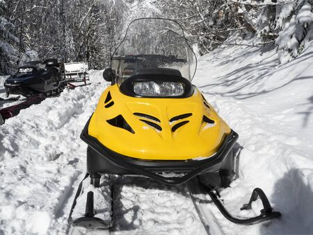 Front view of yellow and black snowmobiles on snow at winter sunny day Stockfoto