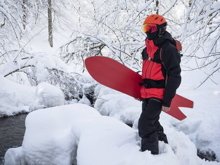 Young active guy with swallowtail snowboard standing in snow at winter forest background Stockfoto