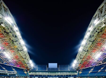 Panoramic view of shiny stadium with seats and empty screen at night sky background