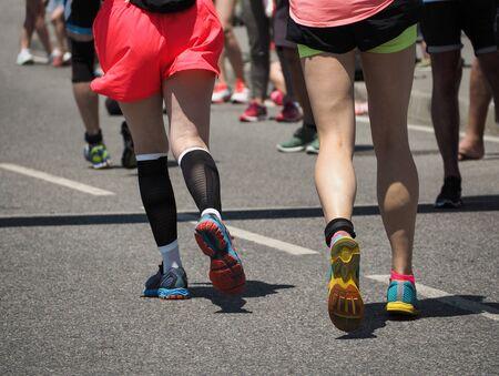 Gruppo di giovani donne in esecuzione in scarpe da jogging su asfalto pista sportiva