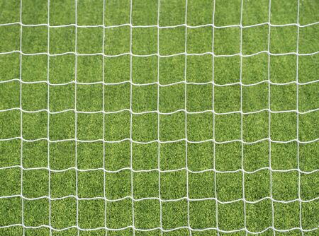 Closeup of goal post net at green football field background. Abstract pattern of sport equipment Stock Photo