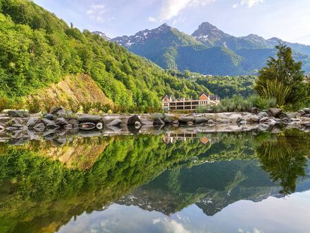 Panoramic view of Rosa Khutor resort in Krasnaya polyana (Sochi, Russia) with mountains reflected on lake water surface
