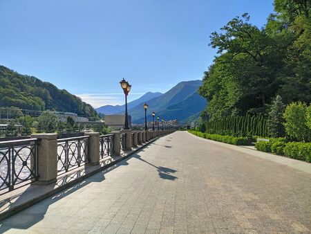 Walking promenade with paving slabs and ornamental trees at mountains background. Sunny day in Krasnaya polyana resort in Sochi, Russia Stockfoto