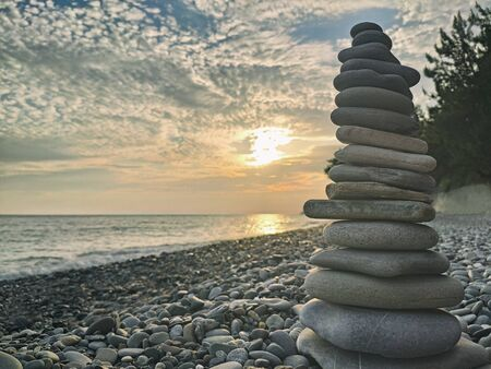 Pyramid of pebble stones on beach at sunset background
