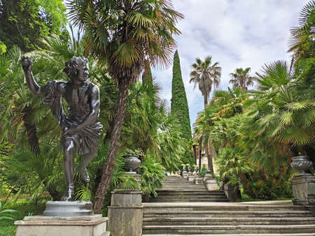 Sochi, Russia - June 21, 2020: Statue at staircase and subtropical trees and palms background in Sochi Arboretum. Famous tourist place in Russia
