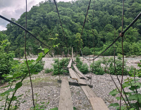 Old hanging bridge with wooden planks over dry river