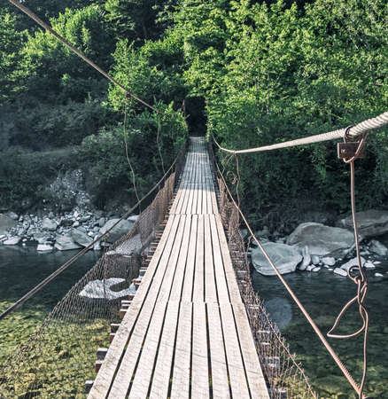Hanging bridge with wooden planks over river water Stockfoto
