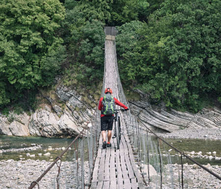 Man walking with cross country bike on suspension bridge over river