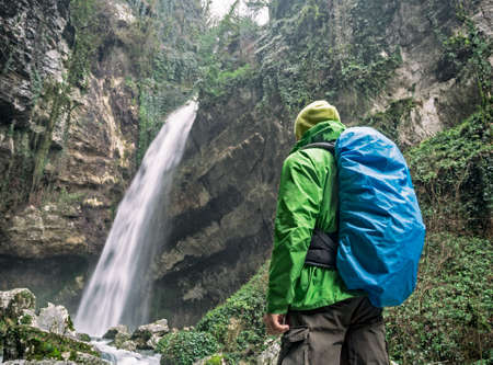Back view of active man with tourist bag with rain cover looking at waterfall