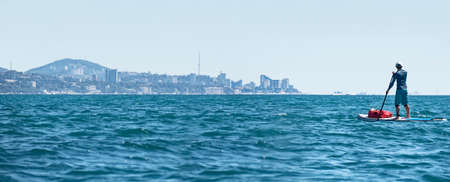 Active man paddling on SUP touring with waterproof bag at Sochi city coastline background