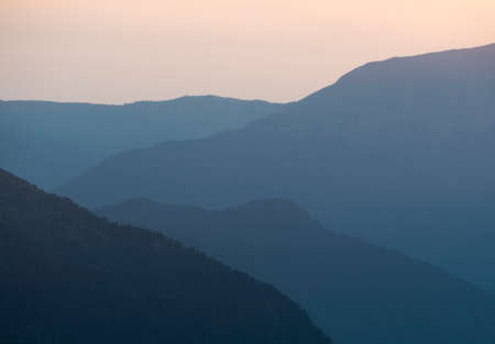 Silhouette of layered mountains ridge at sunset. Blue gradient background Zdjęcie Seryjne