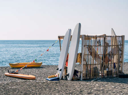 SUP rental station with equipment and accessories for surfing on beach at blue sea background Banque d'images