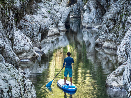 Surfer floating on stand up paddle board on river water in rocky canyon Banque d'images