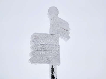 Frozen direction road sign with arrows in snow. Winter background 免版税图像