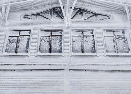 Frozen house with windows covered with frost. Winter background 免版税图像