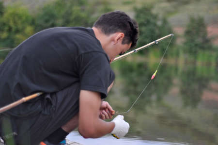 Young man putting worm on fishing rod or pole at water background