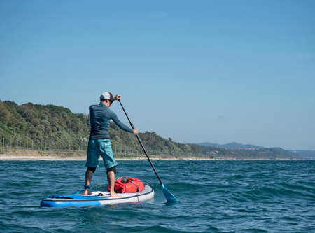 Active man paddling on stand up paddle board on sea water at coast background