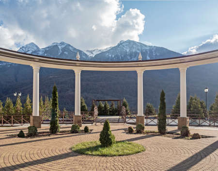 Arch with columns in park at mountains background