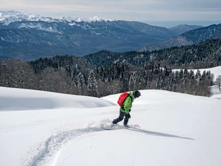Active man riding snowboard on powder snow at mountains, forest and sea background in Krasnaya Polyana, Russia