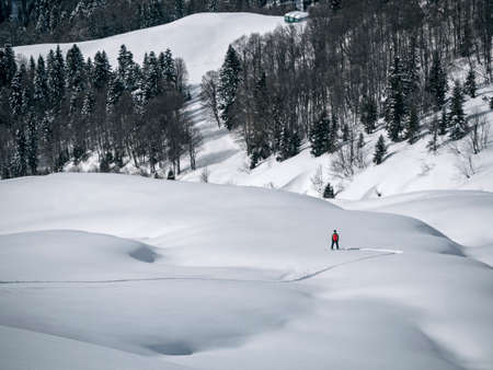 Man freeriding on snowboard and making first track on powder snow. Panoramic winter landscape
