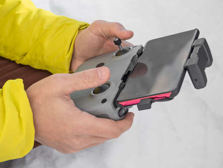 Hands of man holding wireless remote control of quadcopter with smartphone