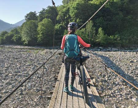 Active woman walking with bicycle on hanging bridge