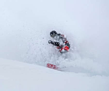 Snowboarder riding and making powder turn in deep snow