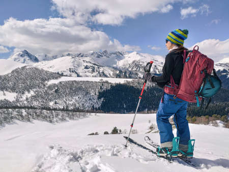 Active woman ski touring on splitboard and looking at panoramic winter mountains background
