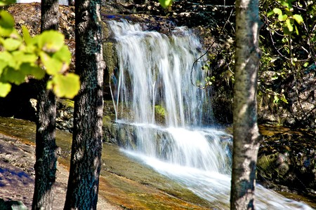 Secluded waterfall seen through the trees on a sunny day. photo