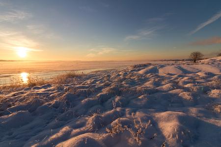 Winter landscape with snow, ocean, sea, blue sky, road, sunshine, ice.